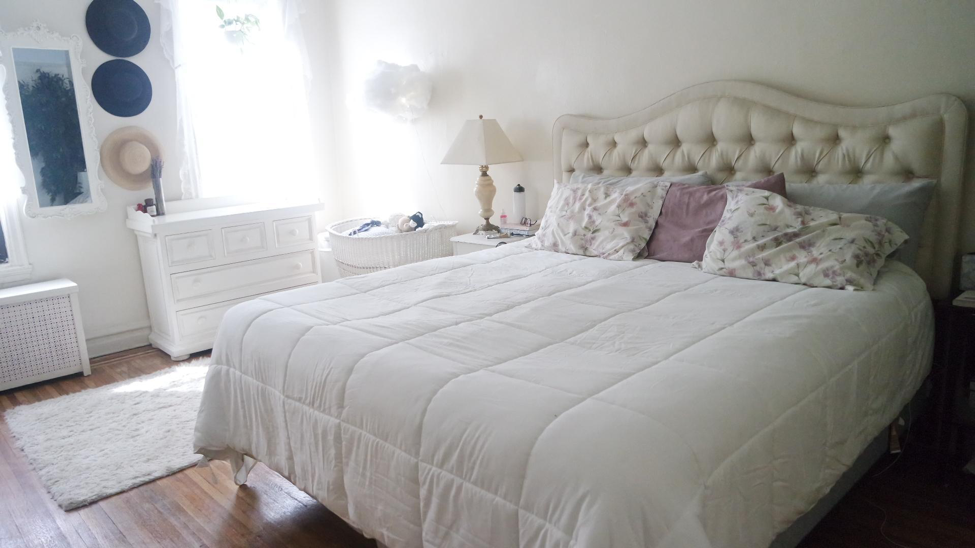 creative bedroom with white bed and white credenza